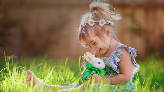 Young girl sitting in grass playing with bunny